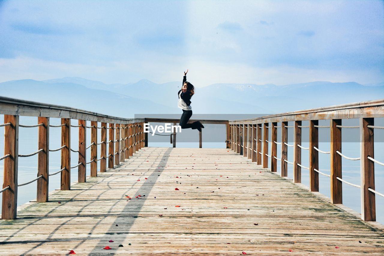 one person, full length, railing, sky, real people, lifestyles, cloud - sky, built structure, leisure activity, architecture, jumping, day, nature, casual clothing, bridge, the way forward, mid-air, mountain, wood - material, outdoors, footbridge, diminishing perspective, human arm