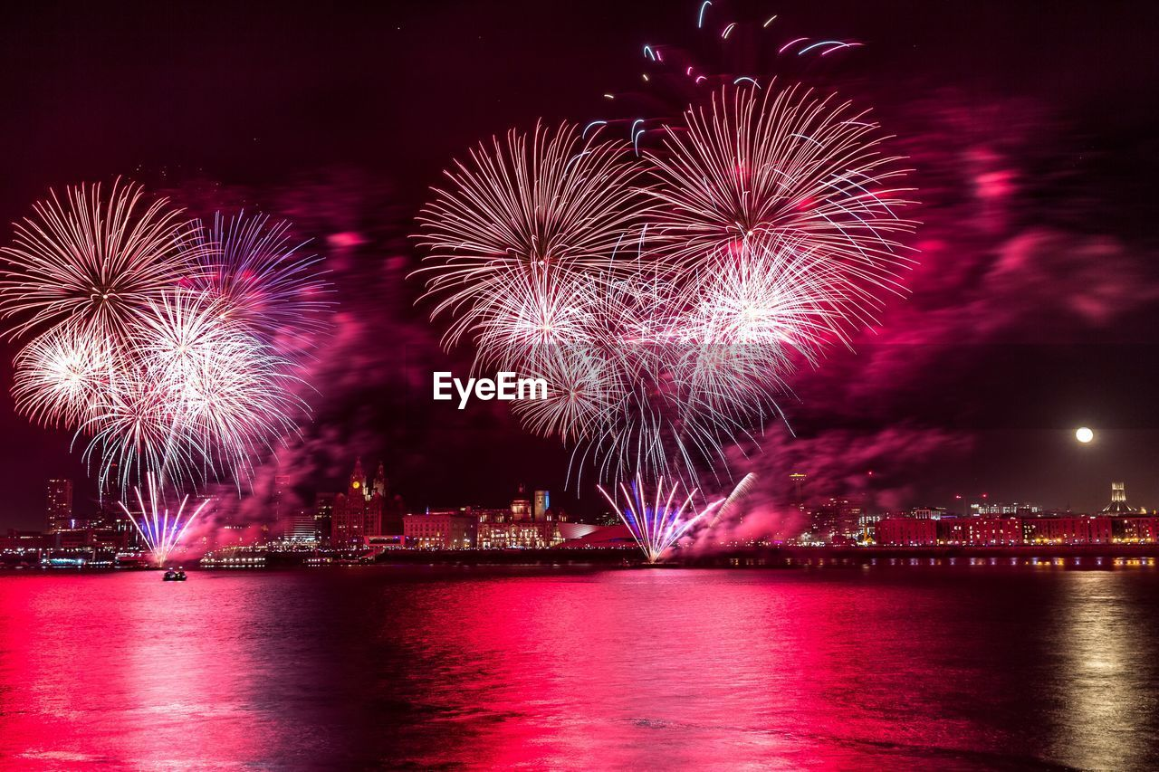 firework, illuminated, night, firework display, exploding, motion, water, arts culture and entertainment, celebration, event, sky, firework - man made object, building exterior, waterfront, long exposure, reflection, architecture, no people, nature, light, outdoors, sparks, cityscape