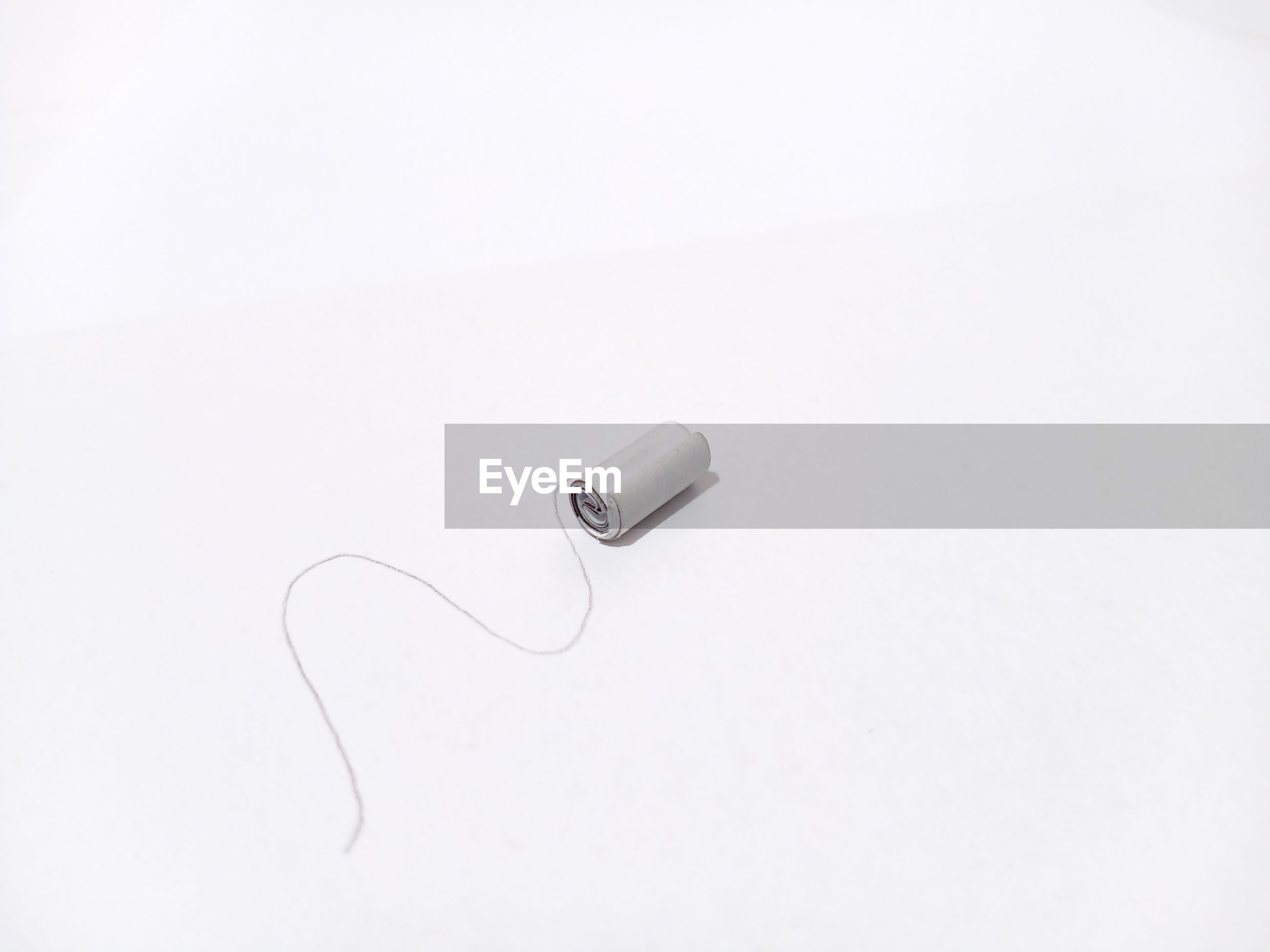 High angle view of rope with rolled paper against white background
