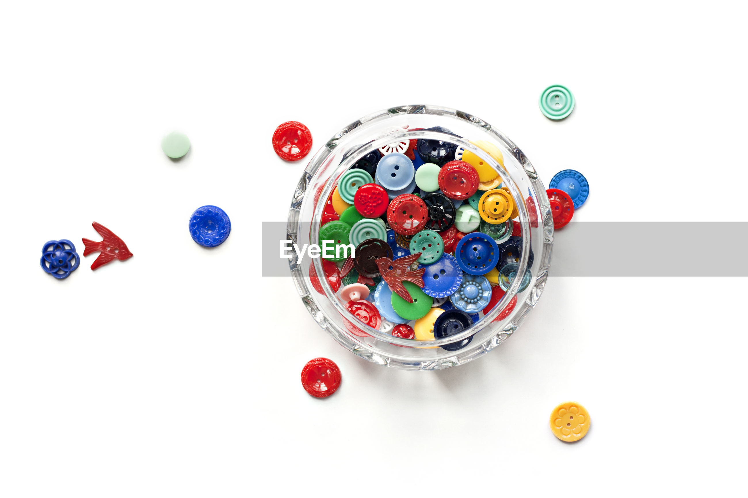 Directly above shot of multi colored buttons with jar over white background
