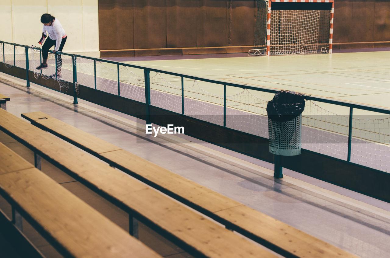 Full length of woman climbing railing at soccer court