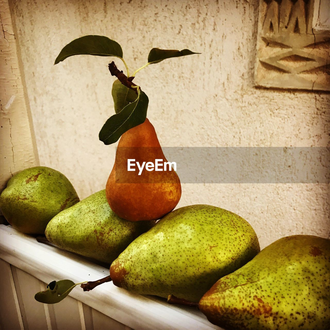 healthy eating, fruit, food, food and drink, freshness, wellbeing, pear, no people, indoors, wall - building feature, still life, green color, wall, close-up, plant stem, leaf, household equipment, table, nature, day, ripe