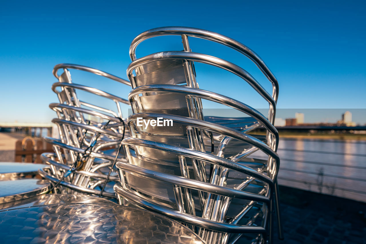 sky, water, metal, nature, blue, clear sky, no people, focus on foreground, architecture, day, built structure, outdoors, close-up, reflection, sunlight, connection, arts culture and entertainment, stainless steel, building exterior, silver colored, steel