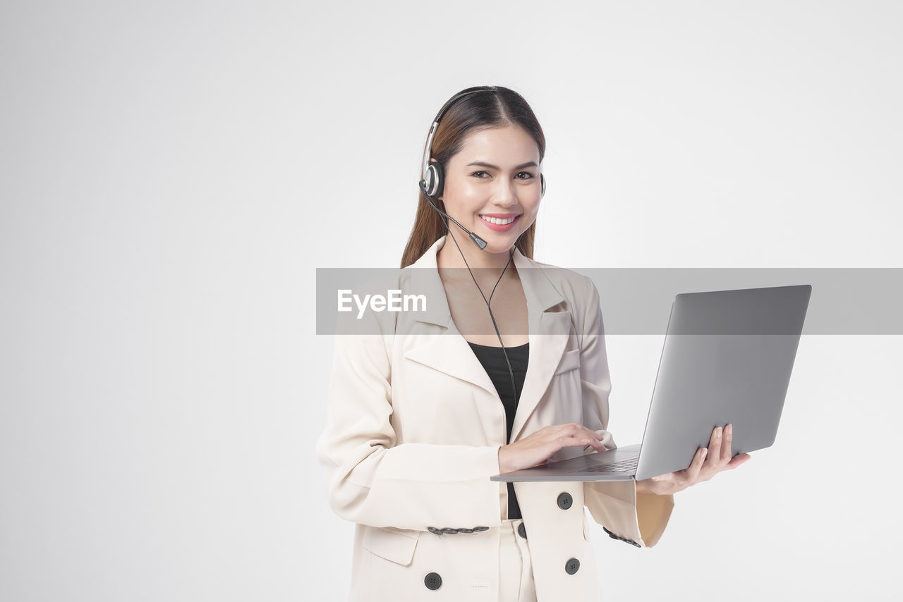 PORTRAIT OF SMILING YOUNG WOMAN USING PHONE AGAINST WHITE BACKGROUND