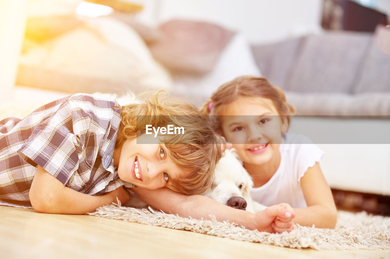 Portrait of smiling siblings with dog relaxing floor at home