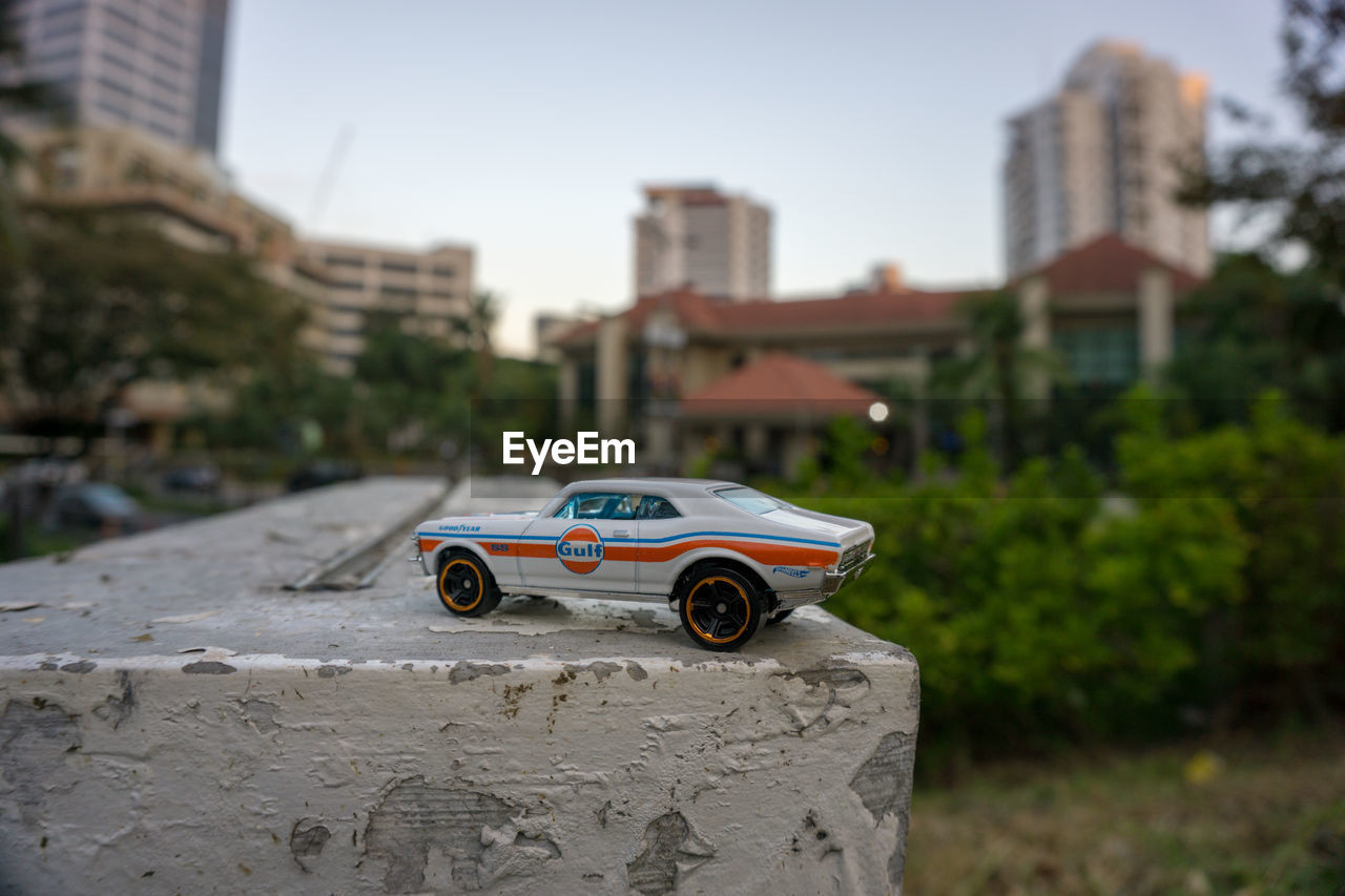 car, mode of transportation, focus on foreground, transportation, toy car, motor vehicle, architecture, built structure, toy, building exterior, day, land vehicle, nature, childhood, city, close-up, creativity, outdoors, selective focus, representation