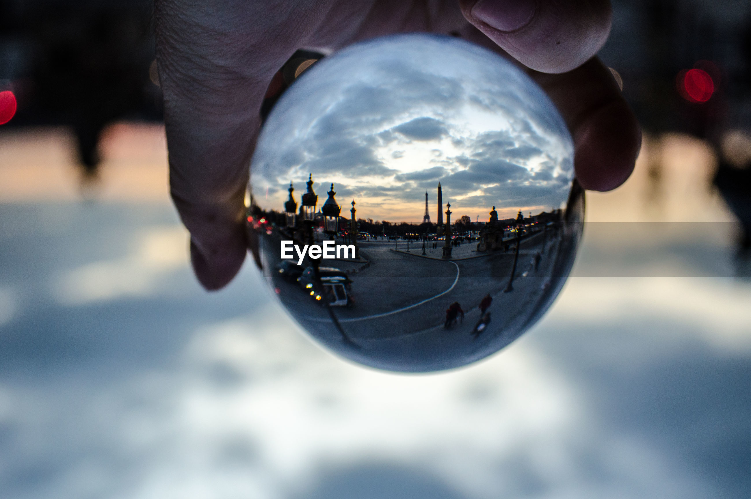 Close-up of hand holding crystal ball in city during sunset