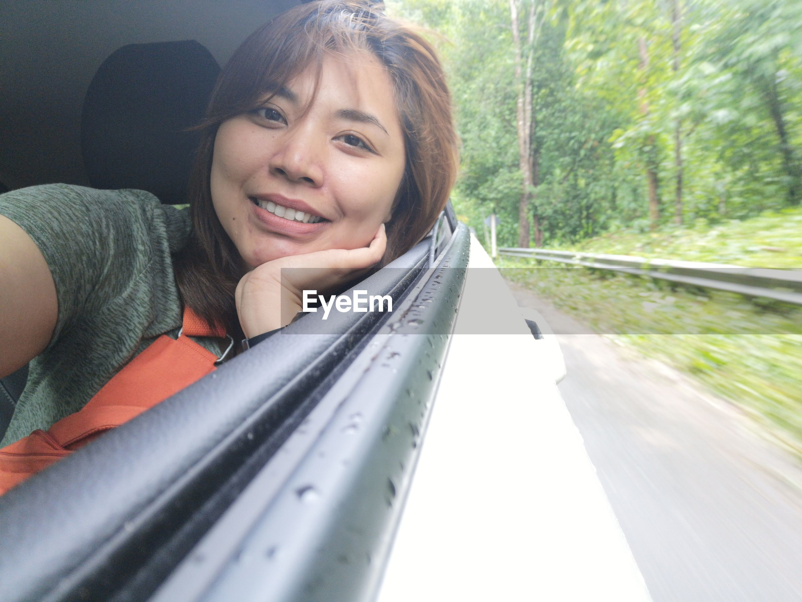 Close-up portrait of smiling woman enjoying road trip in car