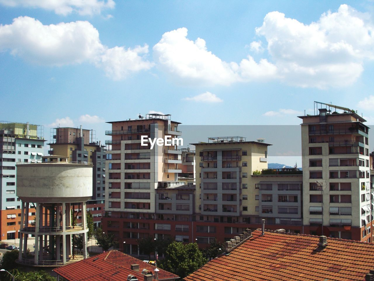 High Angle View Of Residential Buildings Against Cloudy Sky
