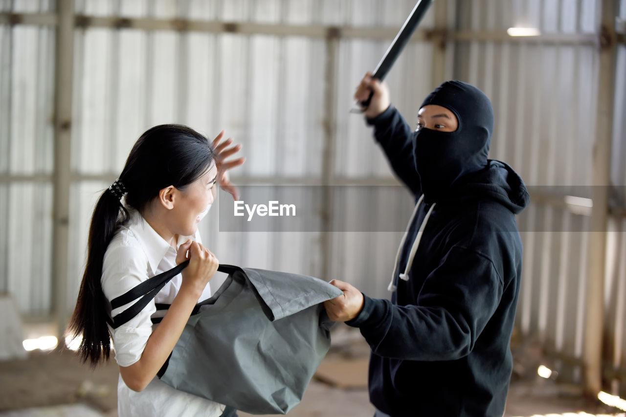 Criminal hitting woman by wood