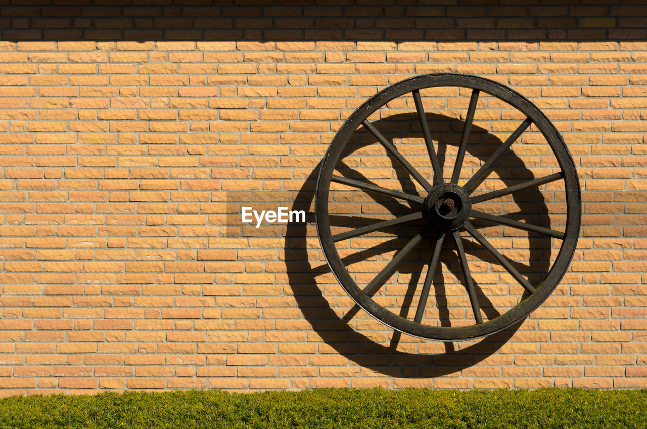 brick wall, wall - building feature, brick, wall, wheel, architecture, sunlight, built structure, day, no people, nature, outdoors, grass, transportation, shadow, building exterior, shape, geometric shape, pattern, circle, cannon, wagon wheel
