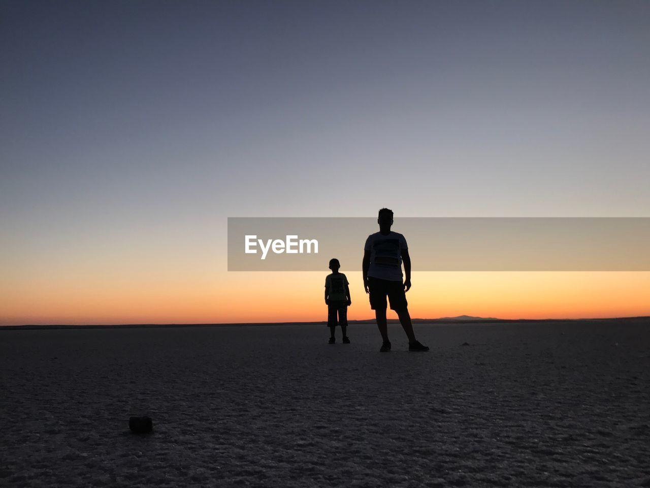 Silhouette father and son standing at beach against clear sky