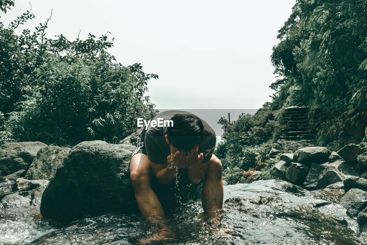 Man Washing Face While Sitting In River
