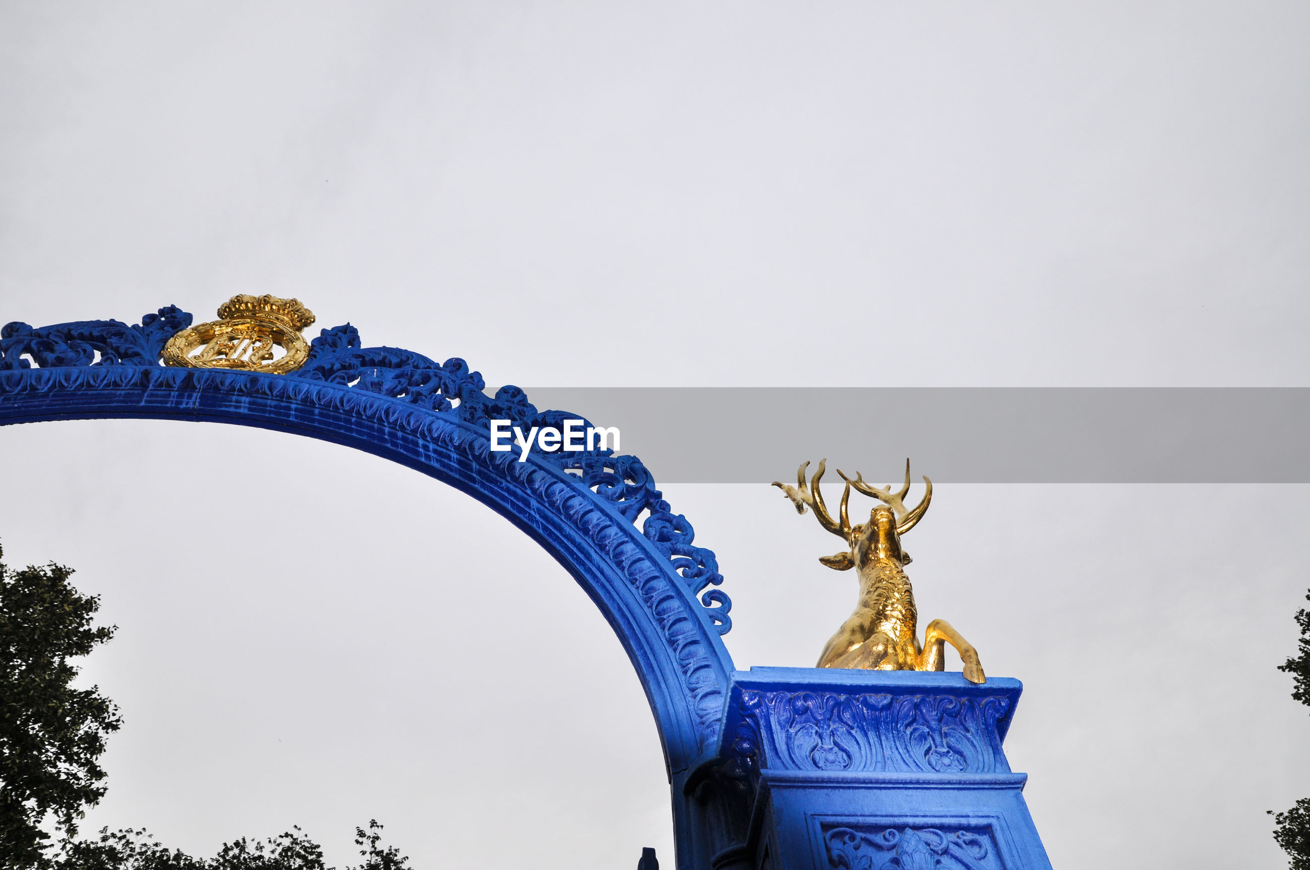 Low angle view of blue gate against clear sky
