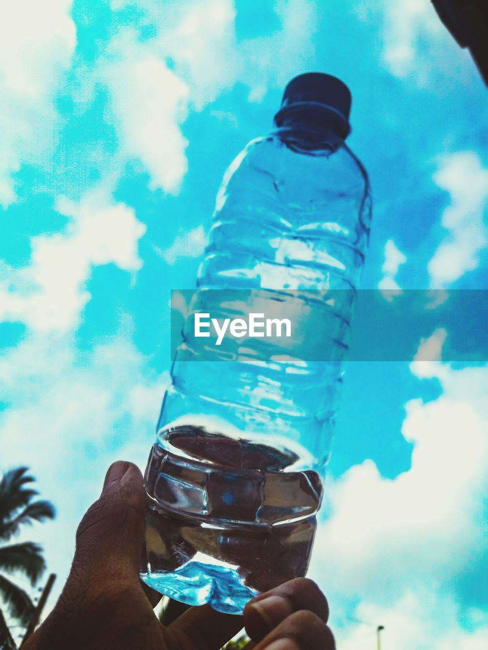 Cropped hand holding water bottle against blue sky