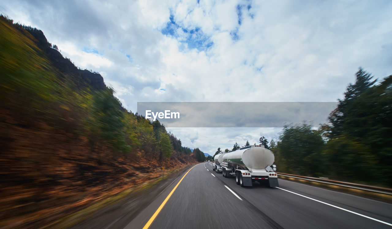 transportation, mode of transportation, motion, road, motor vehicle, land vehicle, sky, cloud - sky, car, blurred motion, on the move, the way forward, direction, nature, no people, marking, travel, road marking, symbol, speed, outdoors, diminishing perspective, road trip, car point of view
