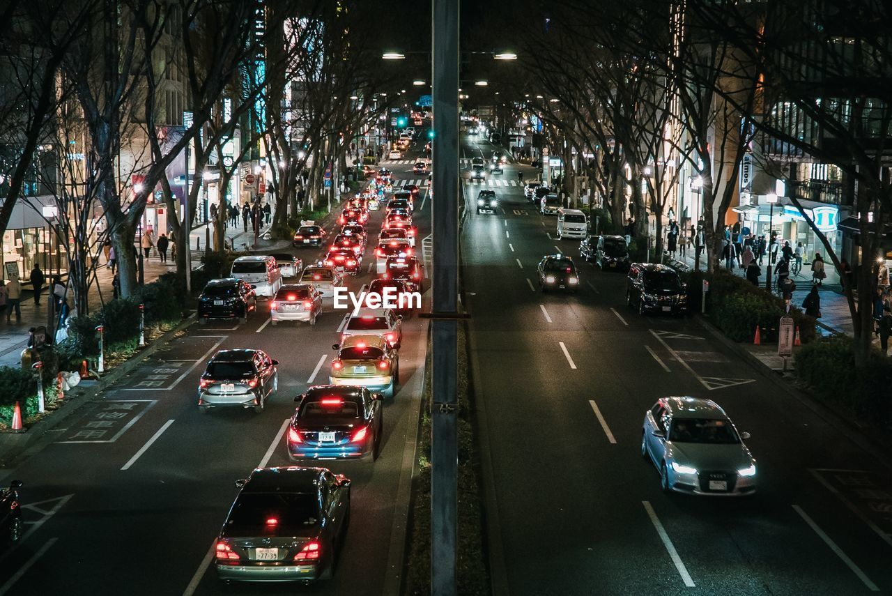 car, mode of transportation, motor vehicle, transportation, land vehicle, city, road, street, architecture, motion, traffic, built structure, illuminated, on the move, building exterior, night, city life, city street, the way forward, symbol, no people, outdoors