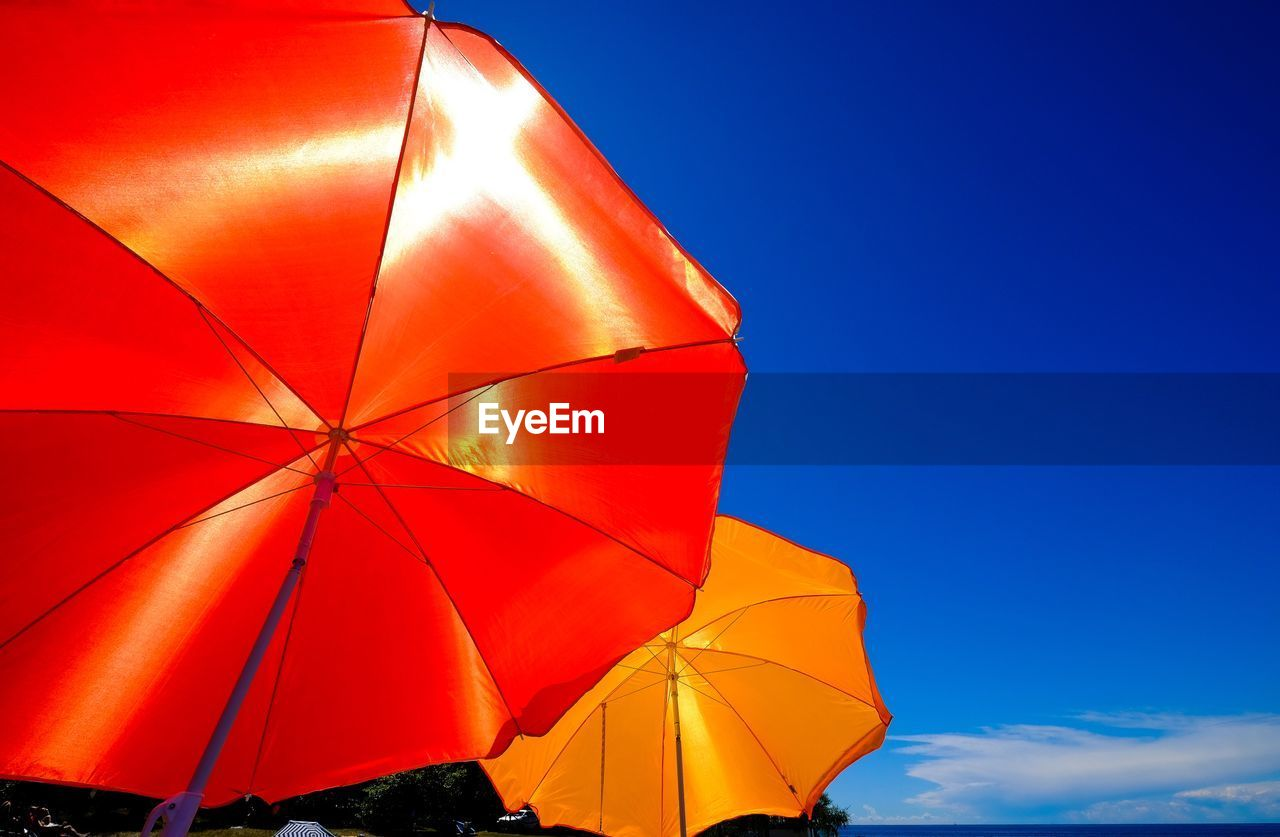 umbrella, protection, security, sky, low angle view, blue, no people, nature, safety, day, parasol, beach umbrella, sunlight, orange color, close-up, outdoors, shade, red, clear sky