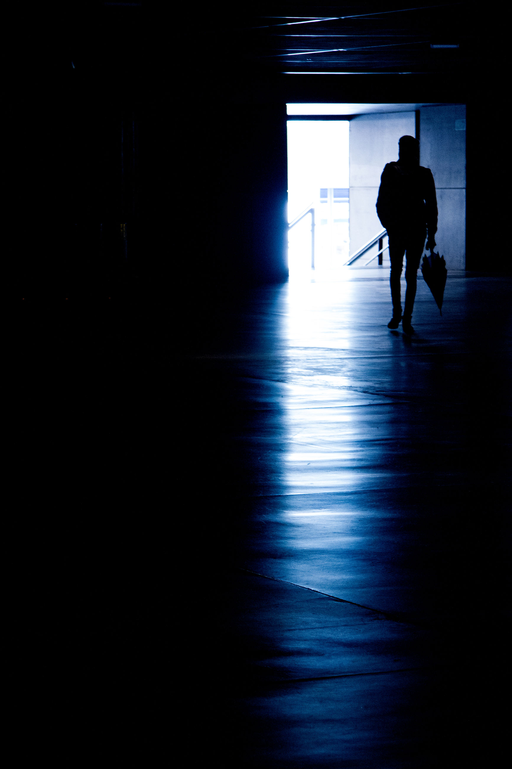 Full length of silhouette man with umbrella in building