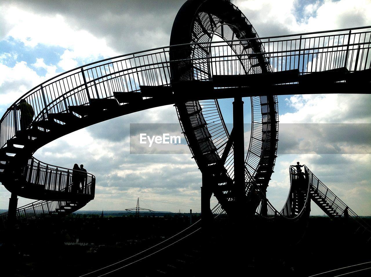 sky, cloud - sky, amusement park, arts culture and entertainment, low angle view, rollercoaster, built structure, amusement park ride, railroad track, bridge - man made structure, big wheel, ferris wheel, outdoors, day, architecture, no people