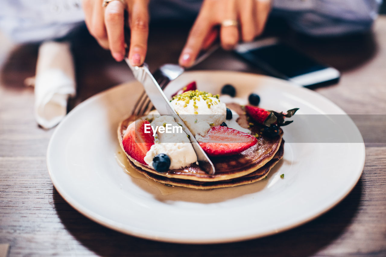 Close-Up Of Hands Eating Pancakes