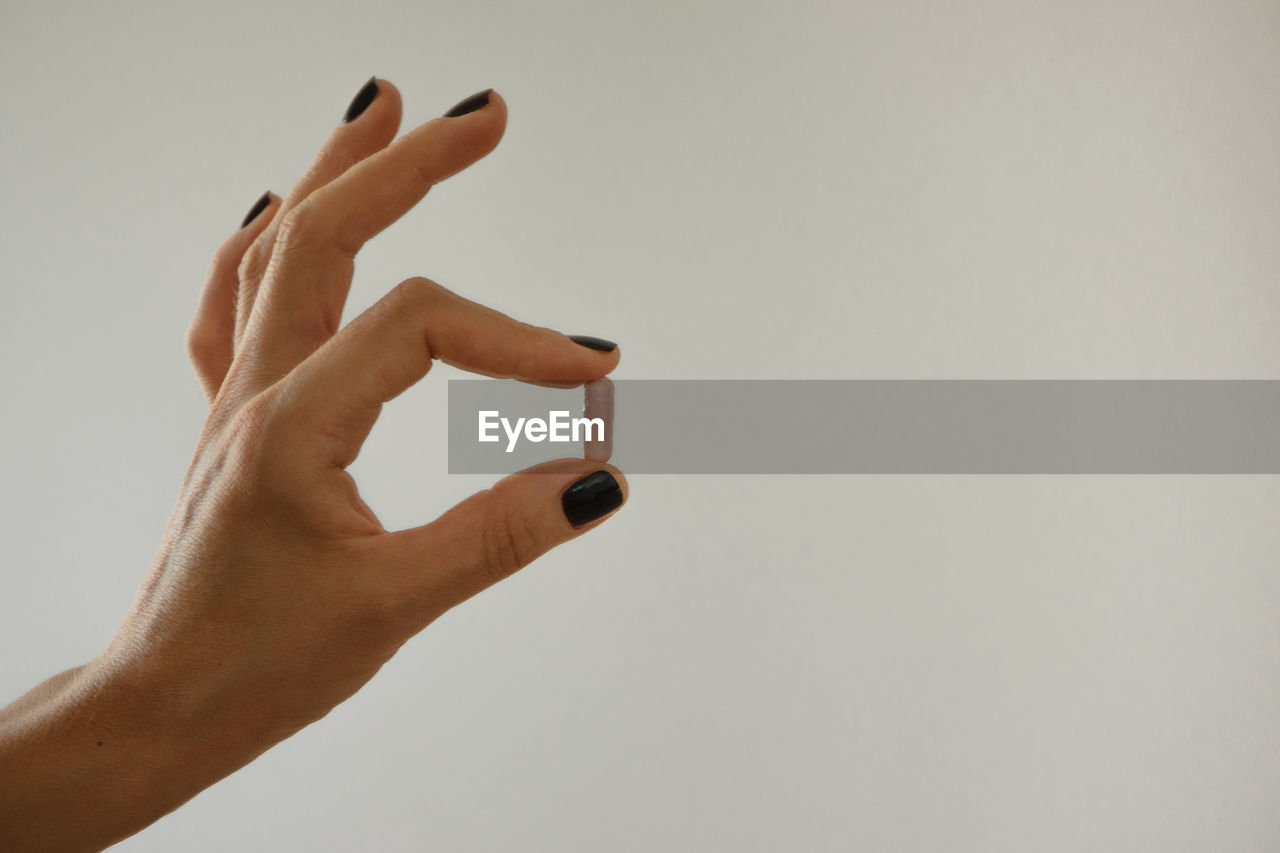 Cropped hand holding pill against white background