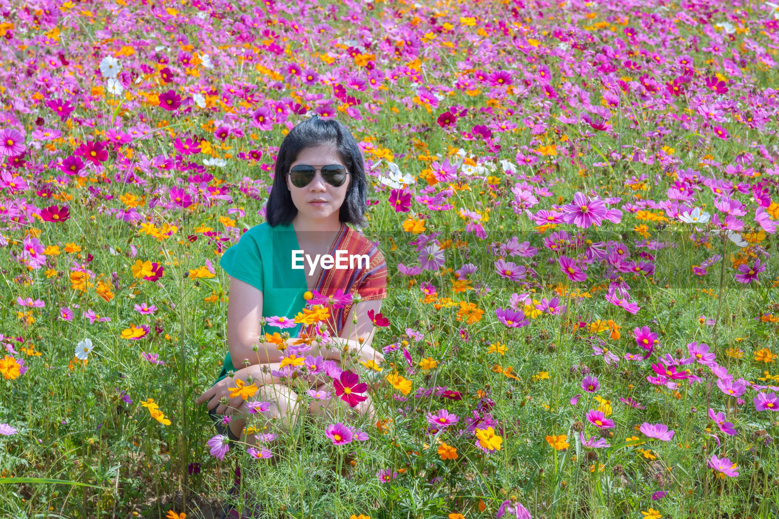 Woman amidst flowers on field