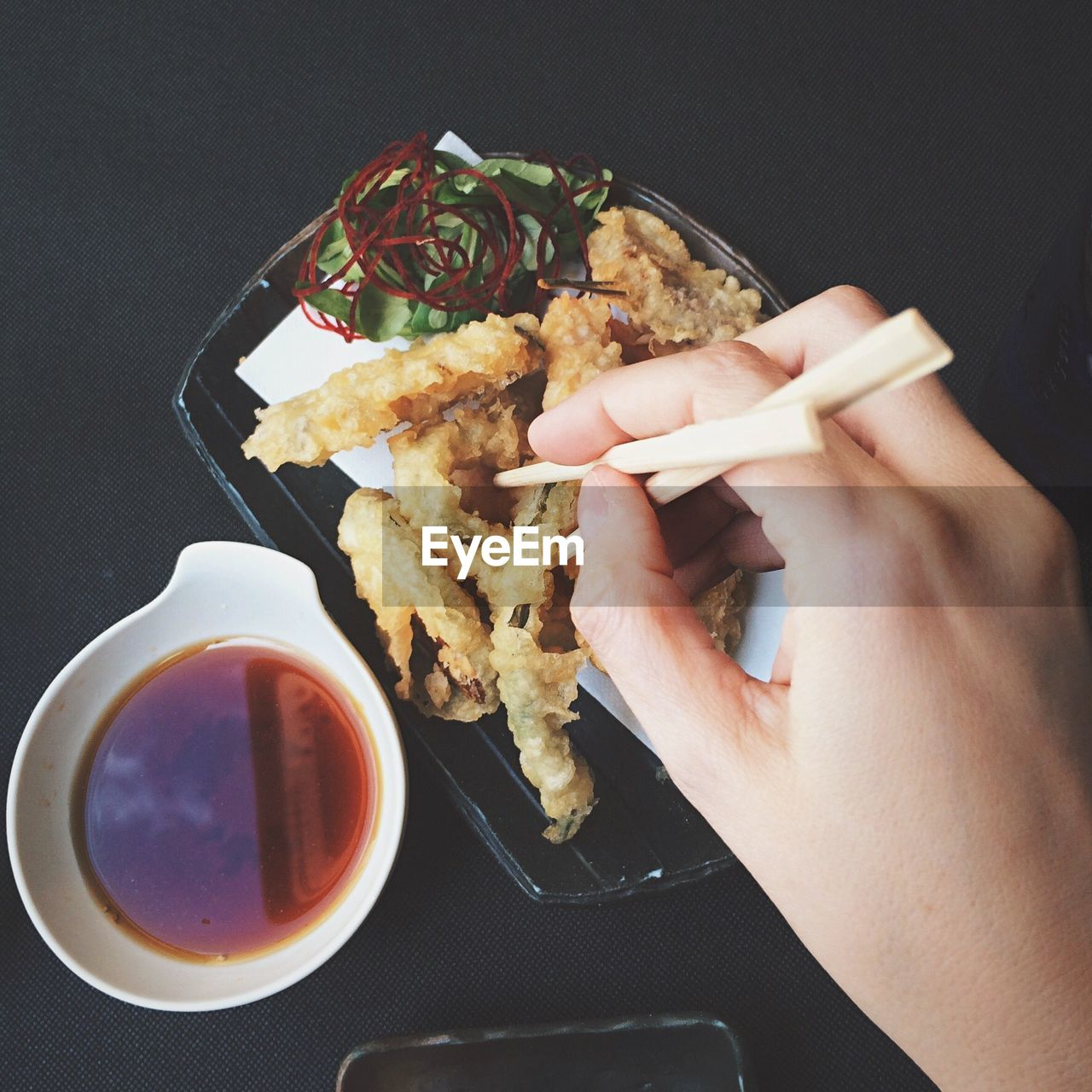Close-Up Of Person Hand Eating Deep Fried Shrimp