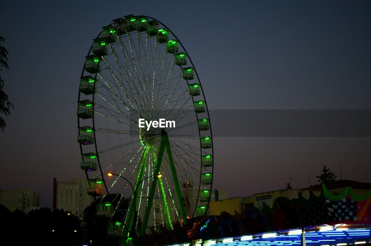 arts culture and entertainment, ferris wheel, amusement park, night, outdoors, clear sky, low angle view, big wheel, no people, illuminated, sky, city, nature