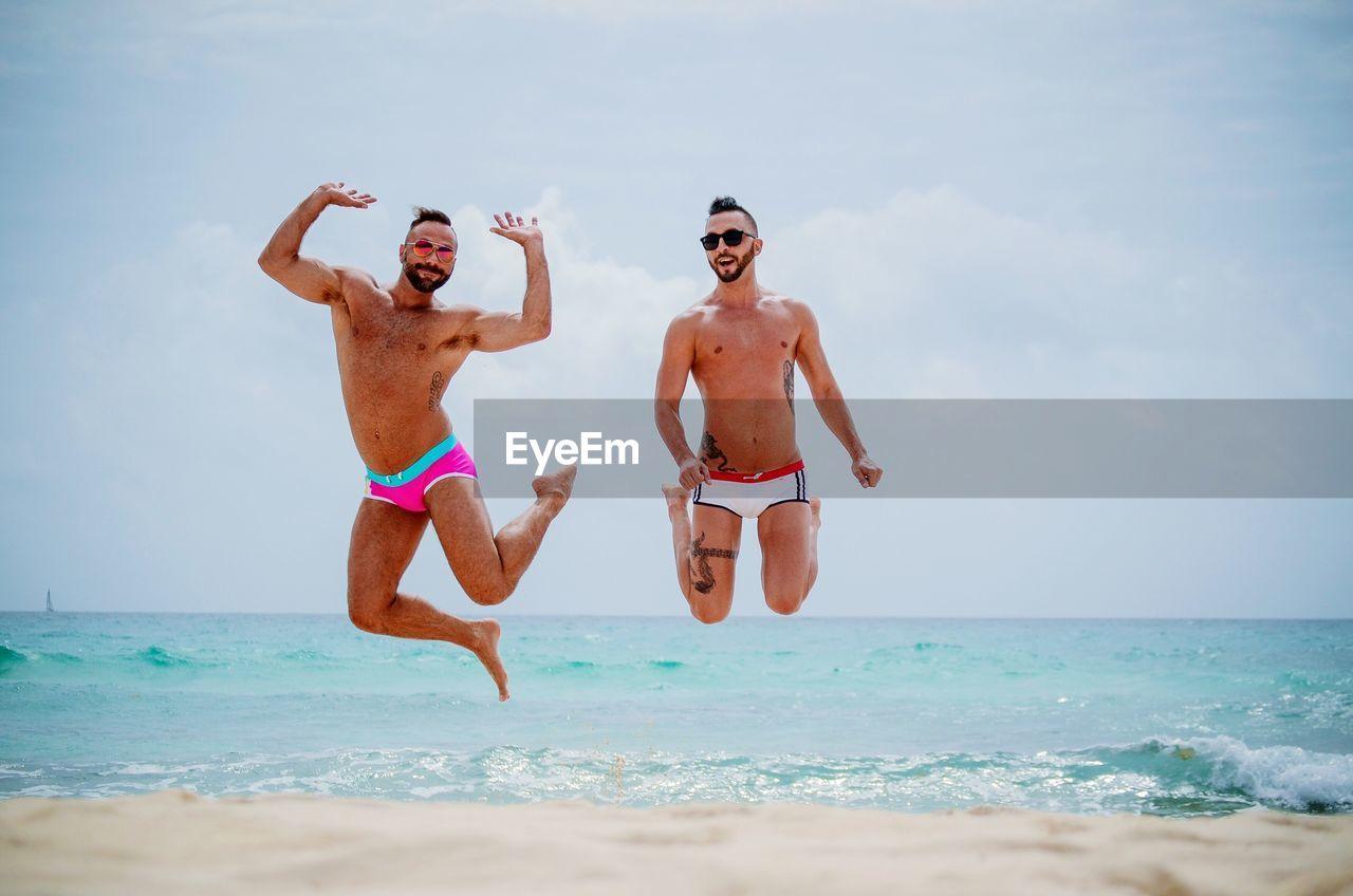 Full Length Of Men Jumping At Beach Against Sky