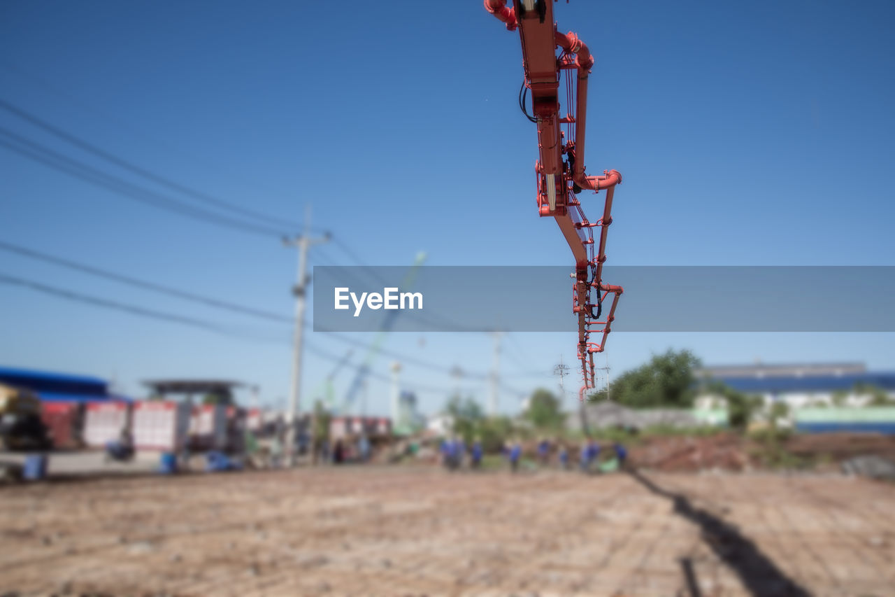 sky, focus on foreground, nature, day, outdoors, land, no people, clear sky, technology, rail transportation, sunlight, cable, field, blue, environment, connection, fuel and power generation, machinery, metal, transportation, electricity, power supply