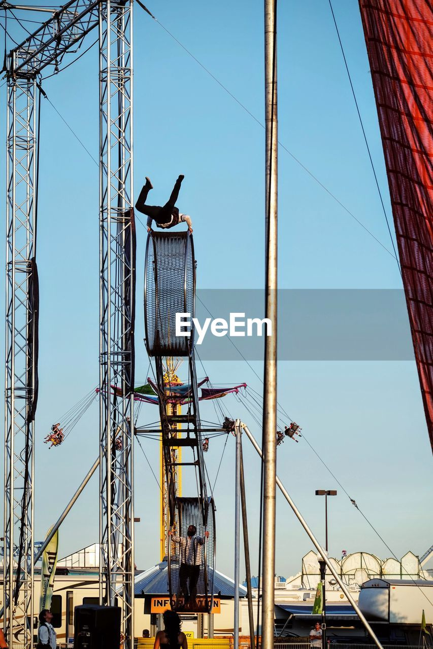 day, sky, clear sky, built structure, outdoors, low angle view, cable, real people, architecture, transportation, nautical vessel, blue, mast, men, nature, people
