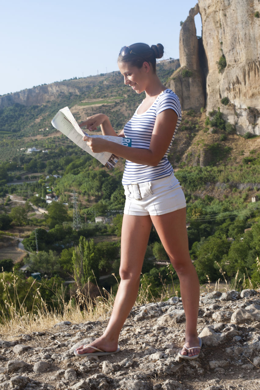 Full Length Of Young Woman Reading Map While Standing On Mountain
