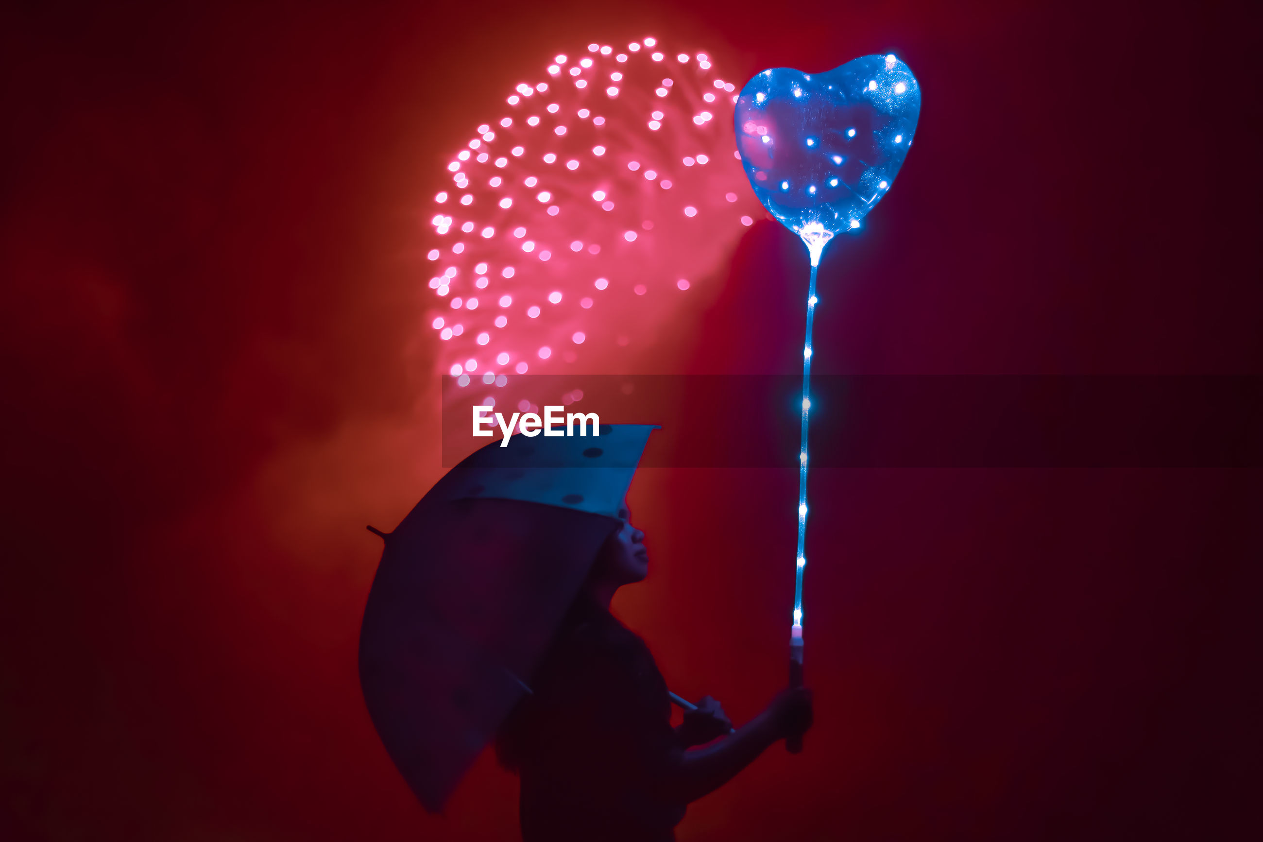 Woman holding umbrella and illuminated balloon while standing outdoors