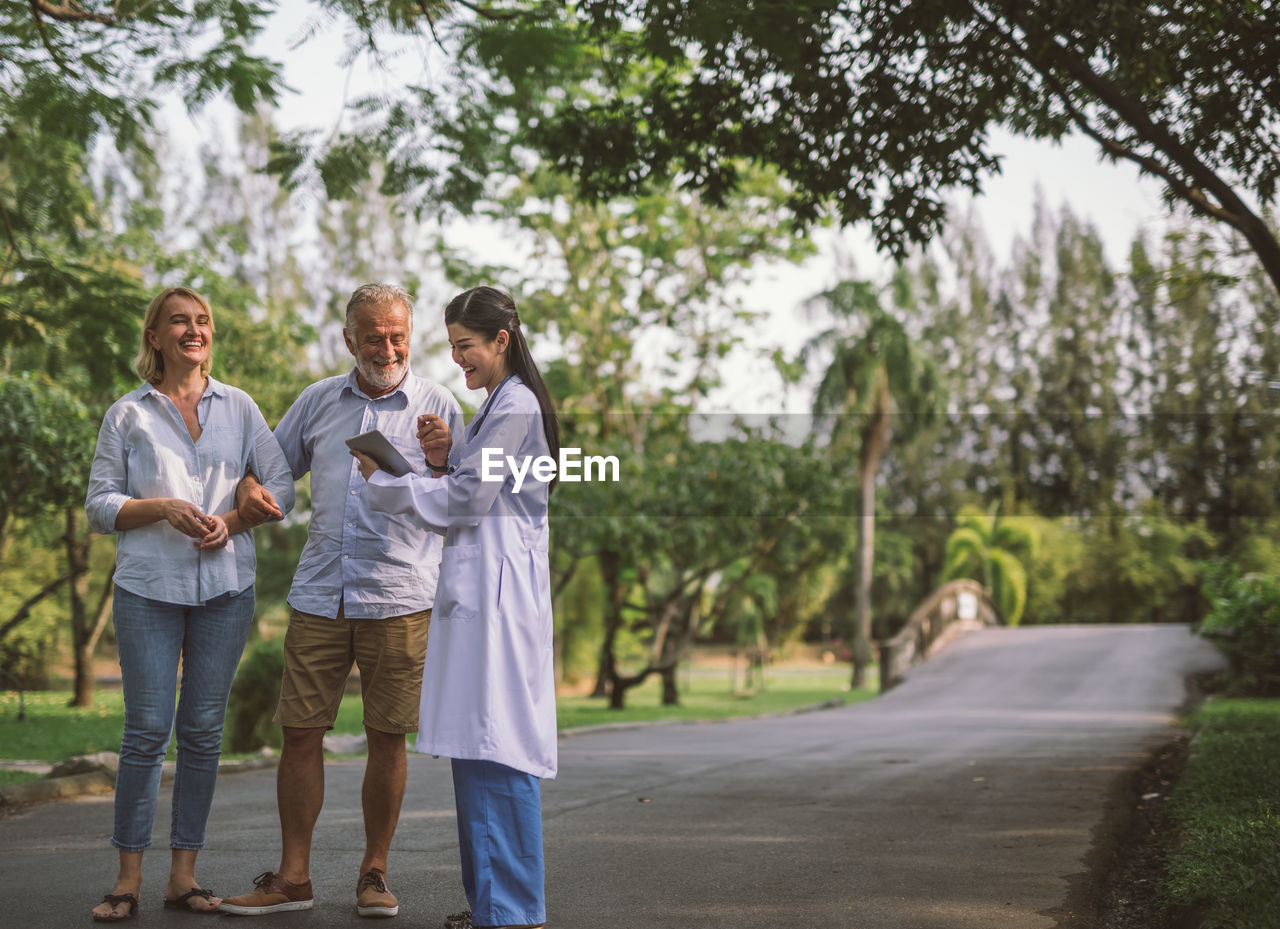 Happy Couple Discussing With Doctor On Road At Park