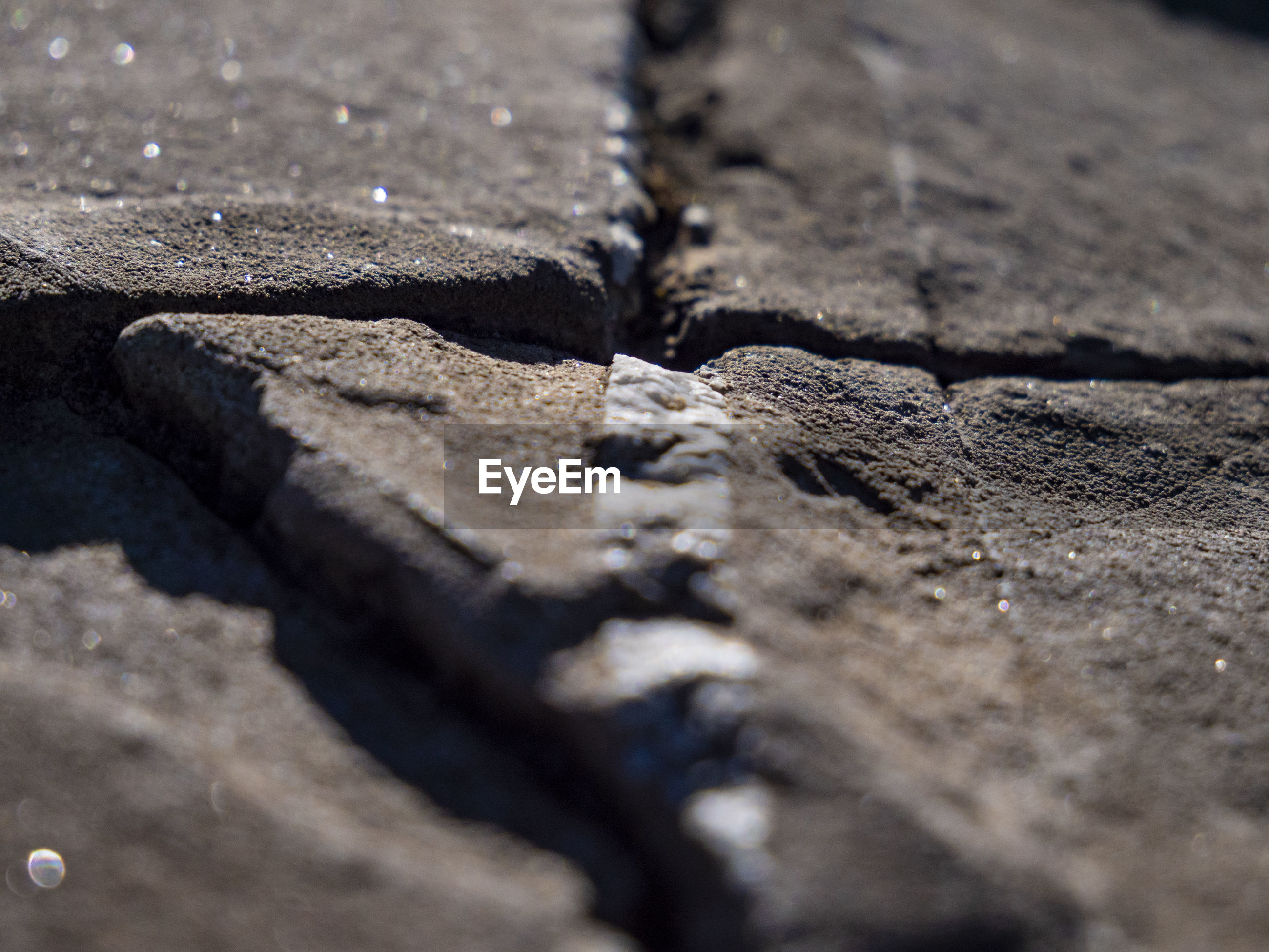 Full frame shot of cracked footpath during sunny day