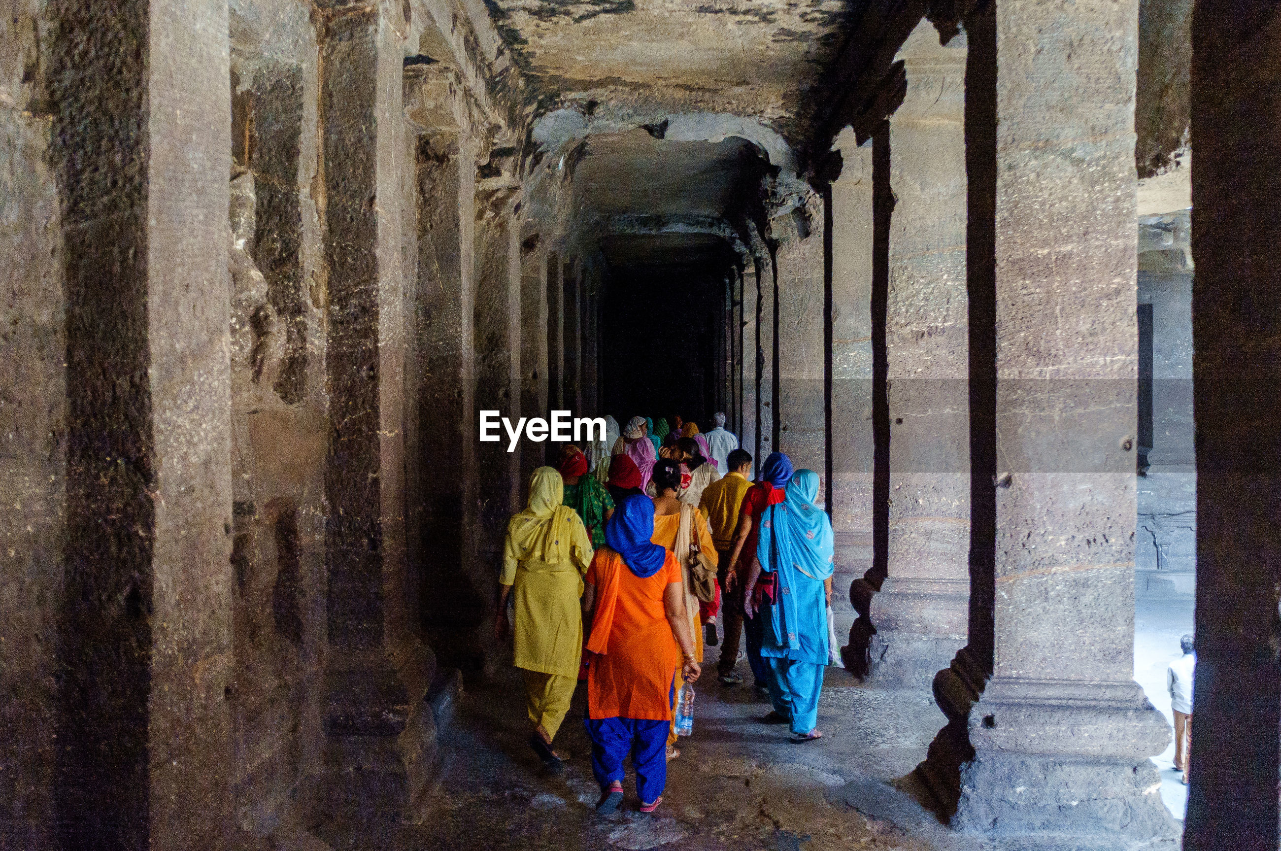Rear view of people walking in old temple