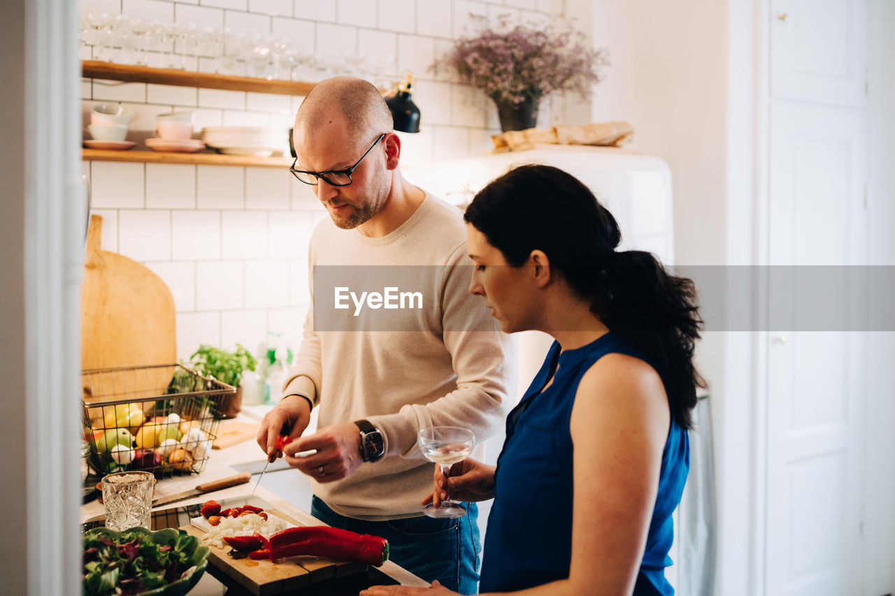 Woman with wineglass looking at male friend cutting pepper in kitchen