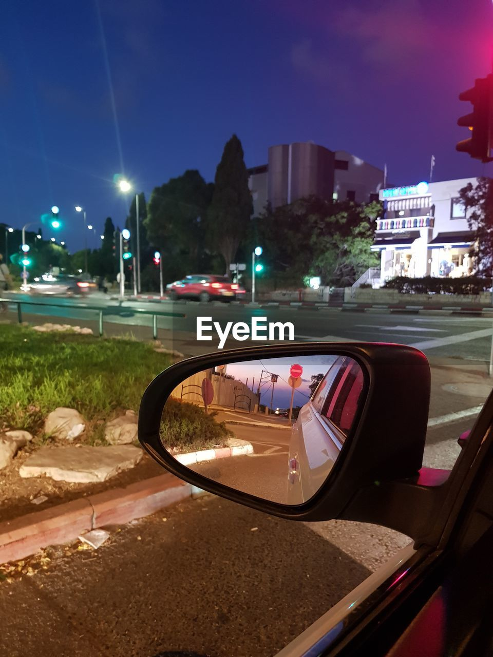 mode of transportation, car, motor vehicle, transportation, city, architecture, building exterior, land vehicle, built structure, reflection, sky, nature, street, road, no people, side-view mirror, illuminated, outdoors, tree, night, vehicle mirror
