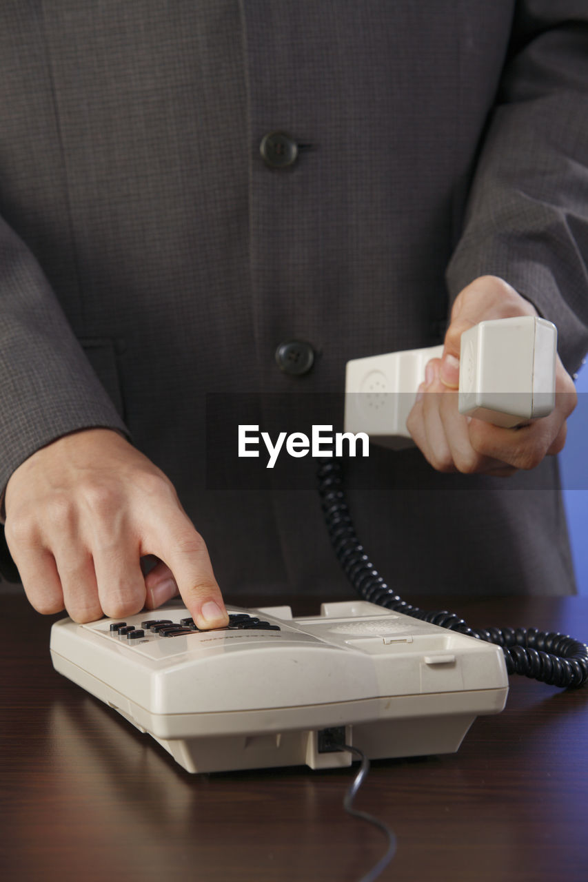 Midsection of businessman holding telephone