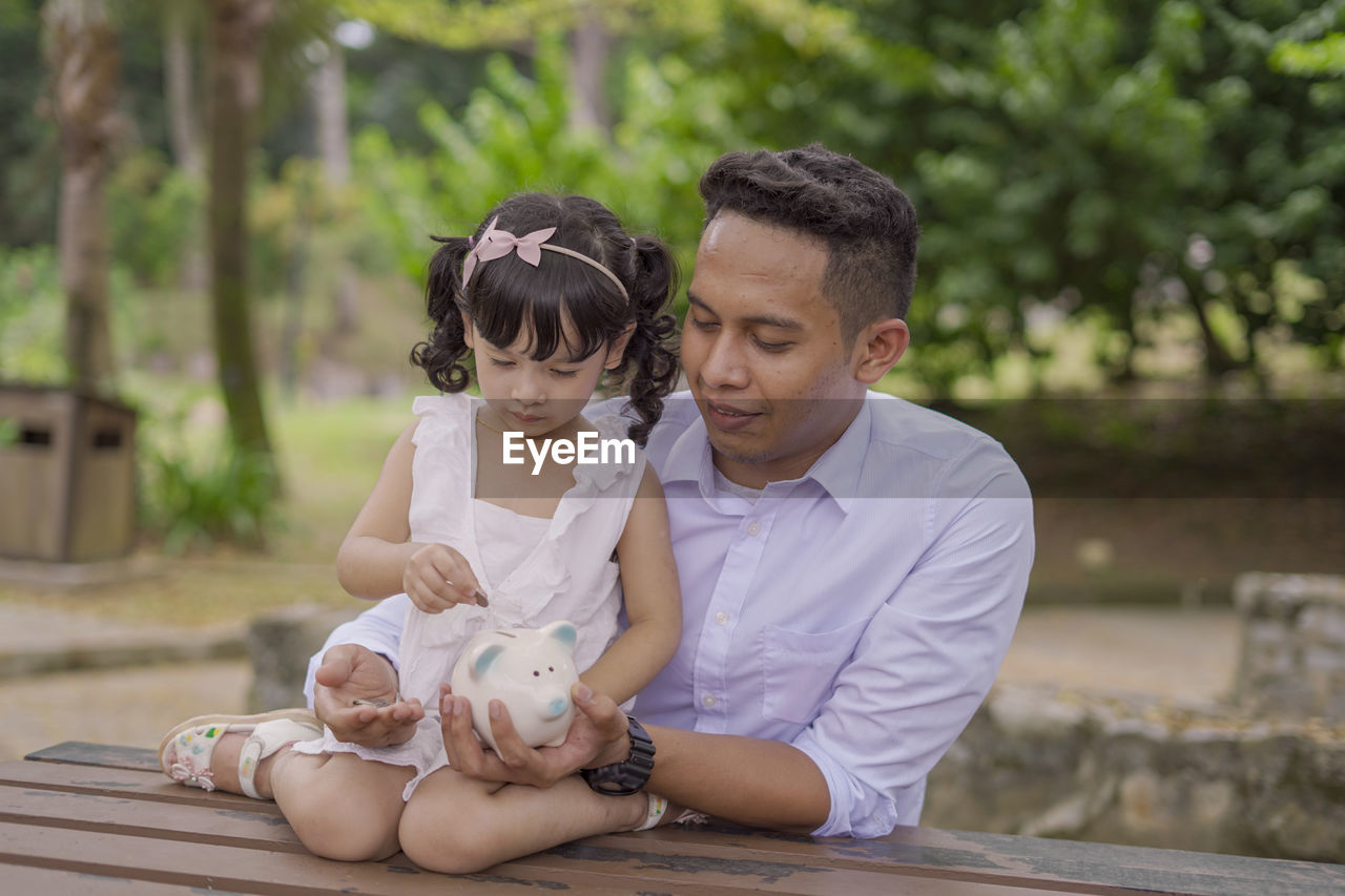 child, childhood, togetherness, real people, two people, females, lifestyles, women, sitting, males, men, bonding, girls, front view, leisure activity, focus on foreground, family, day, people, innocence, positive emotion, outdoors