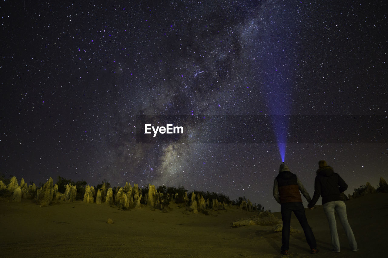 Rear View Of Couple Standing On Landscape Against Star Field