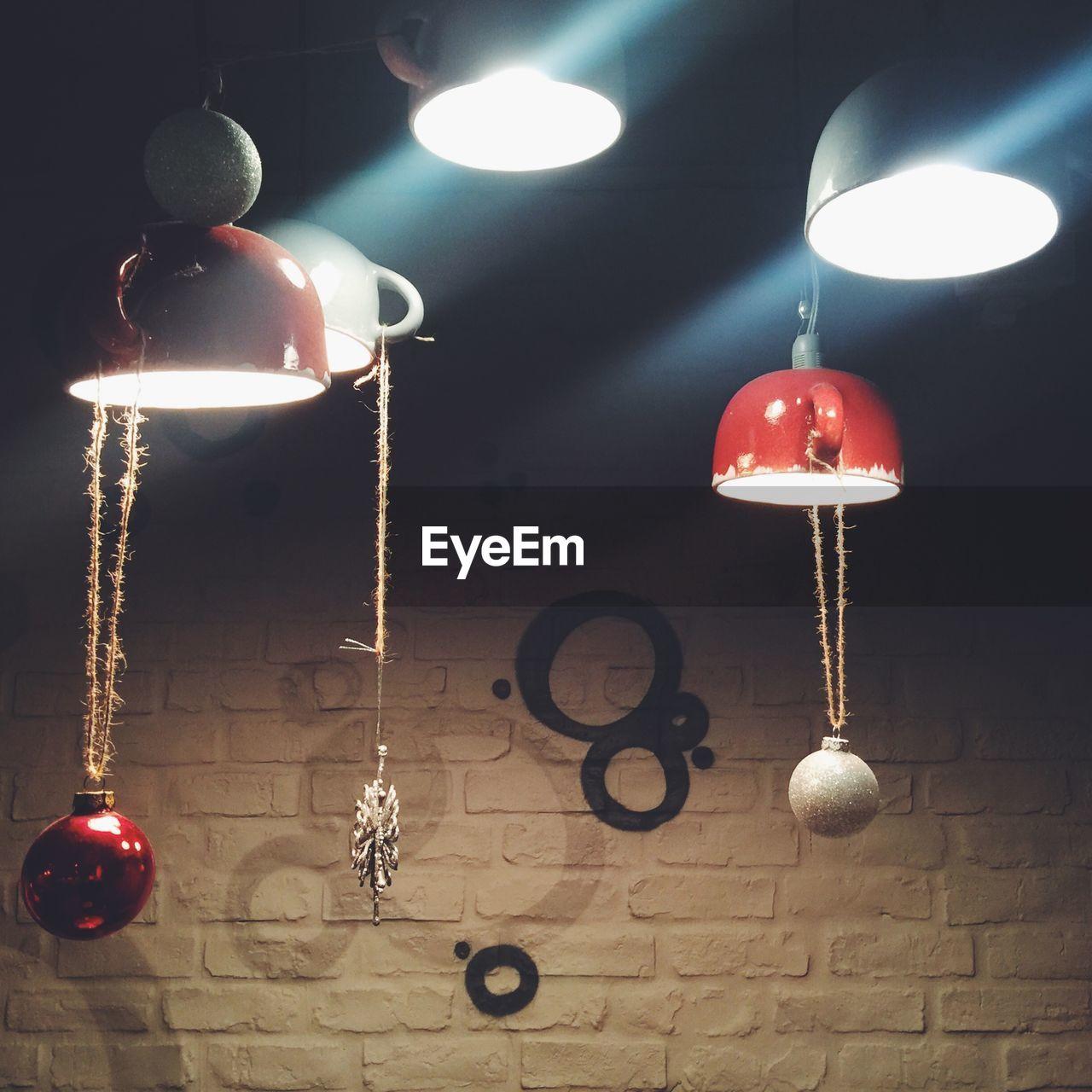 ILLUMINATED LAMP HANGING IN ROOM