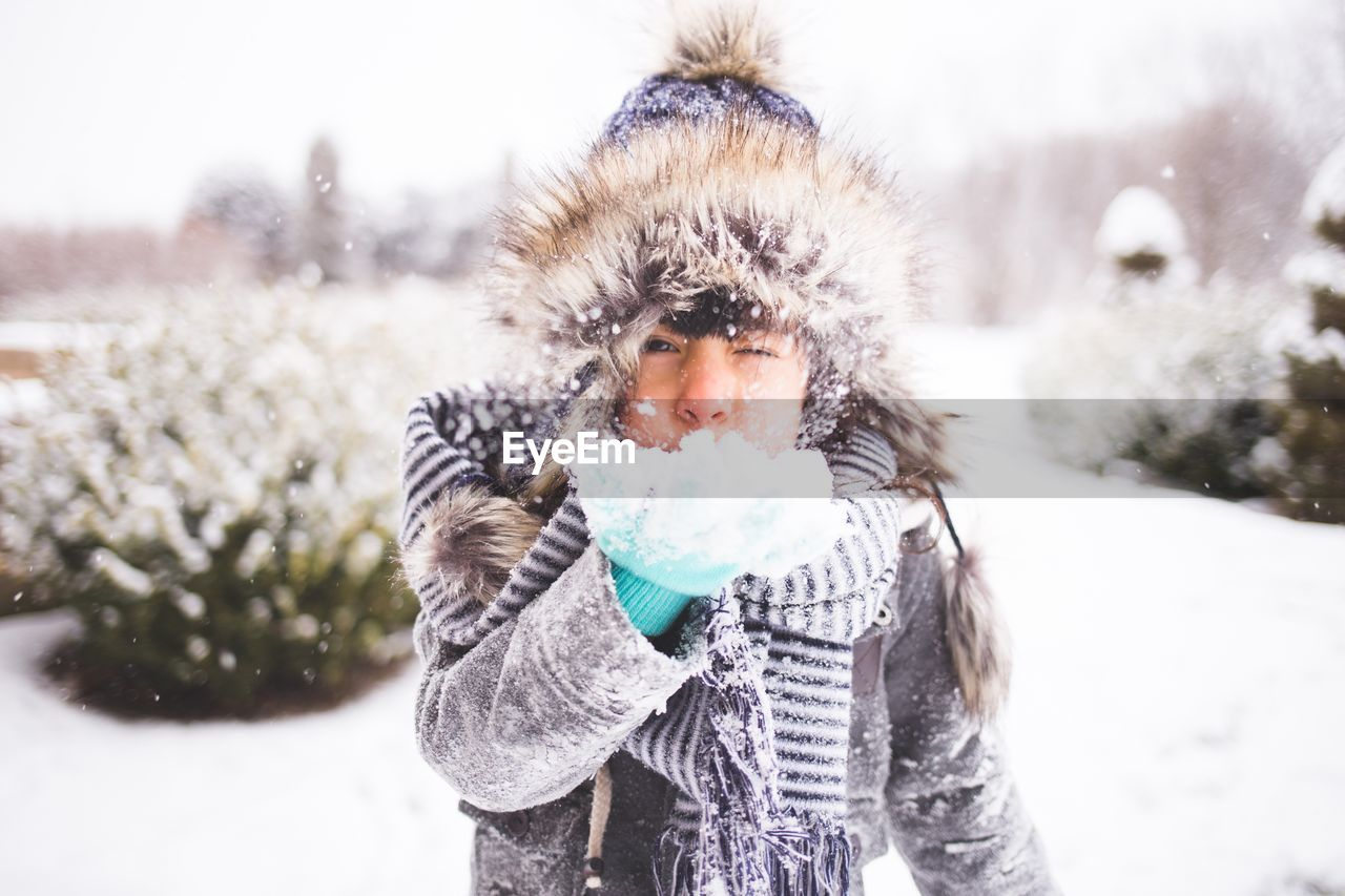 Portrait Of Girl Blowing Snow During Winter