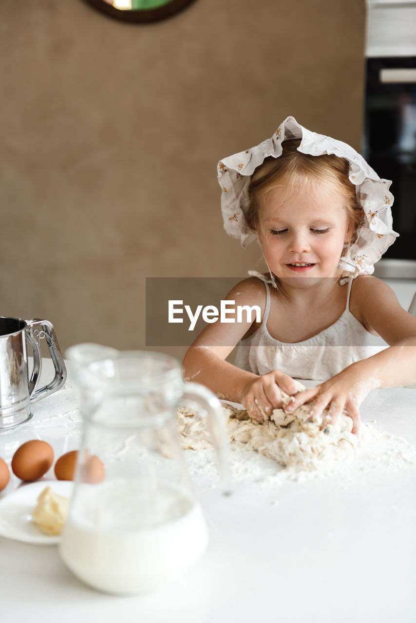 PORTRAIT OF CUTE GIRL HAVING FOOD ON TABLE