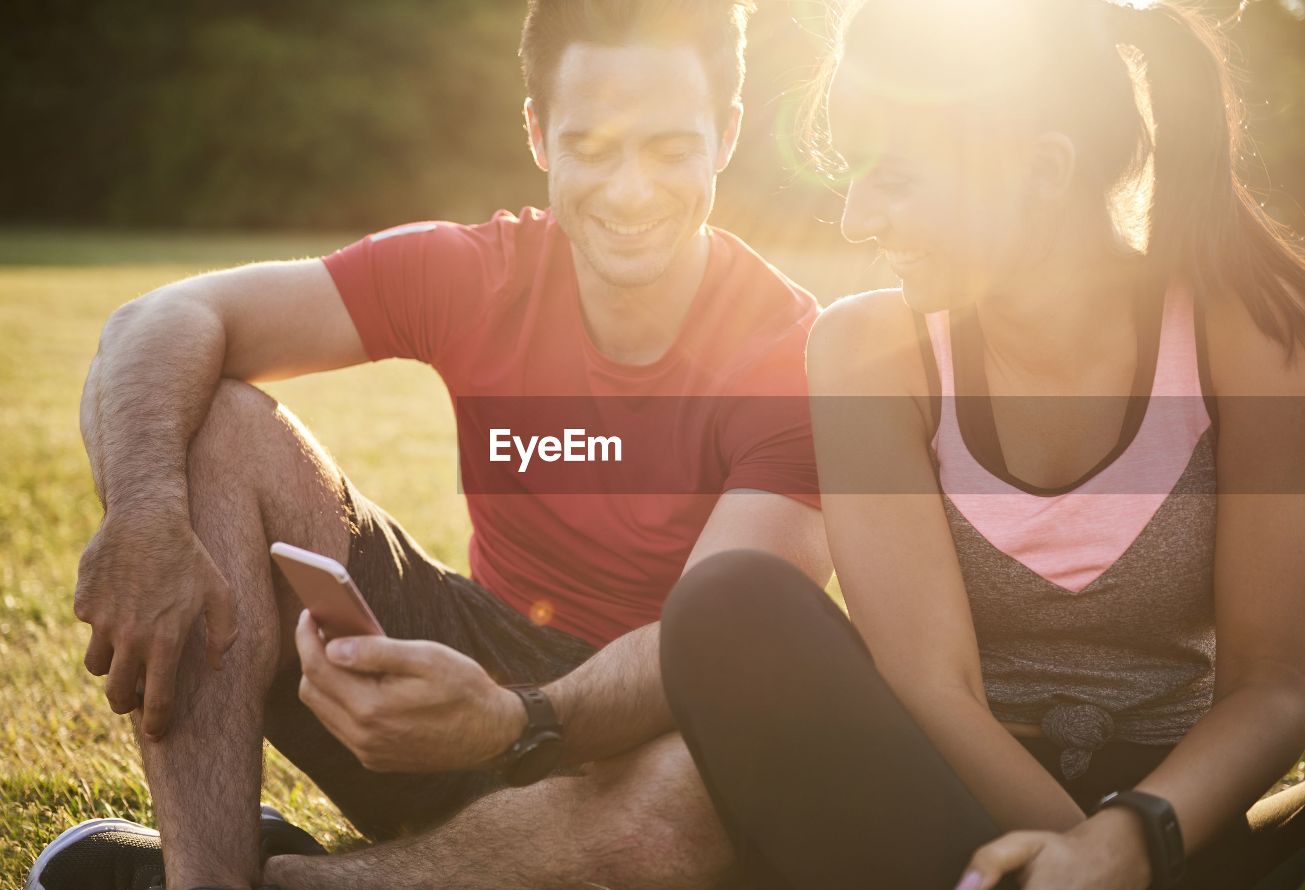 Smiling friends using smart phone while sitting at park