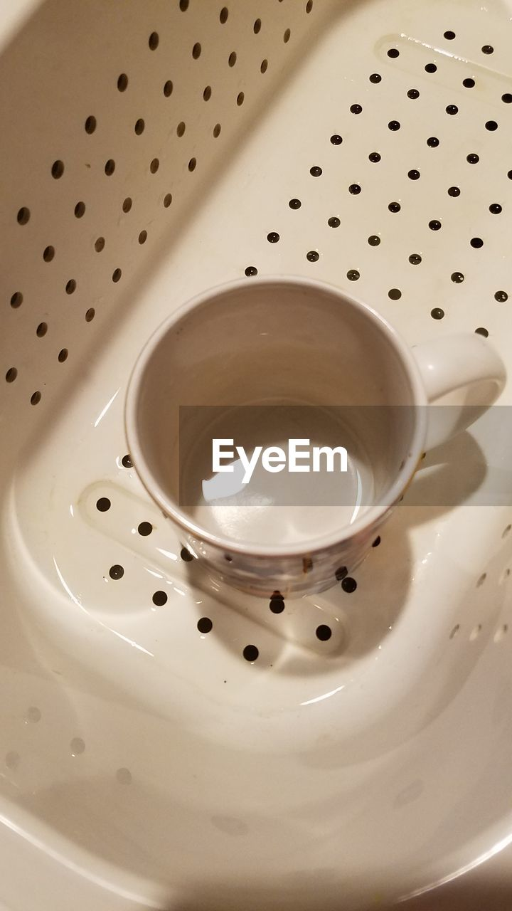 indoors, high angle view, no people, close-up, white color, food and drink, still life, household equipment, hole, sink, cup, empty, metal, water, domestic room, mug, refreshment, ceramics, pattern
