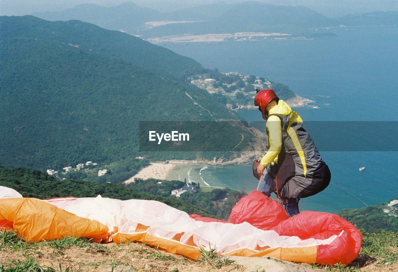 Man With Parachute Standing On Mountain