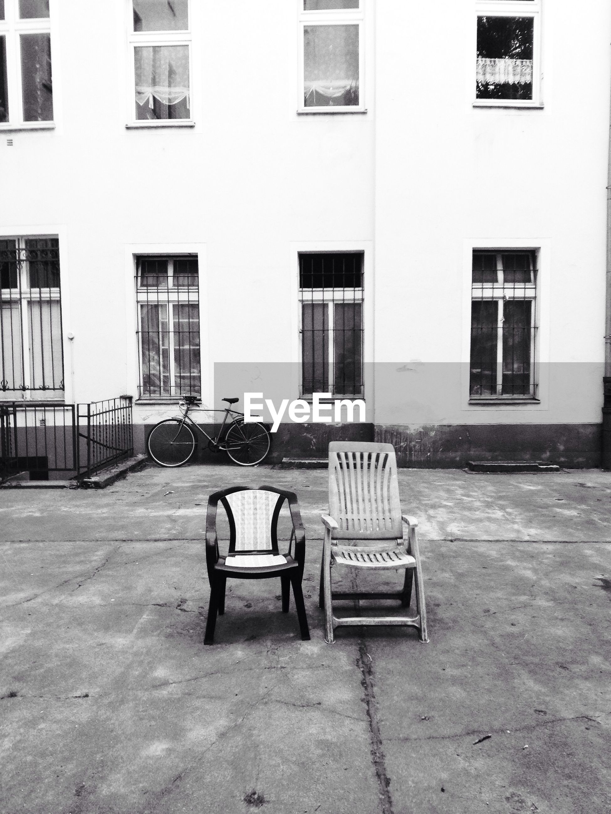 Empty chairs on street against building