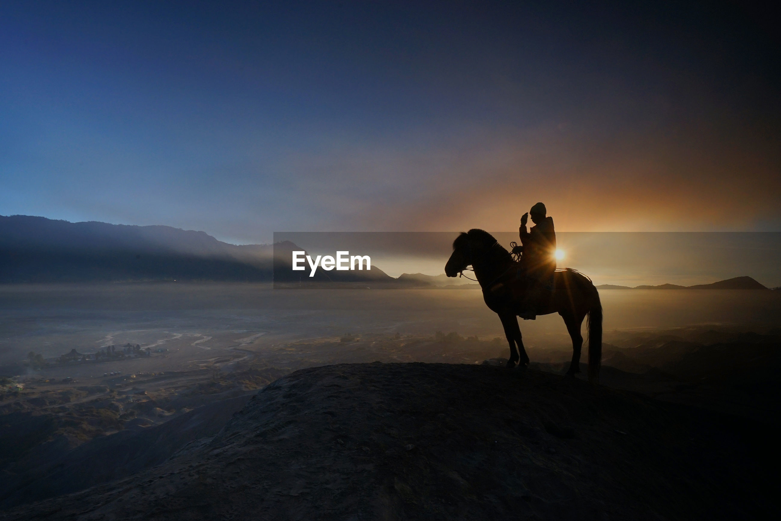 Silhouette man sitting on horse over mountain